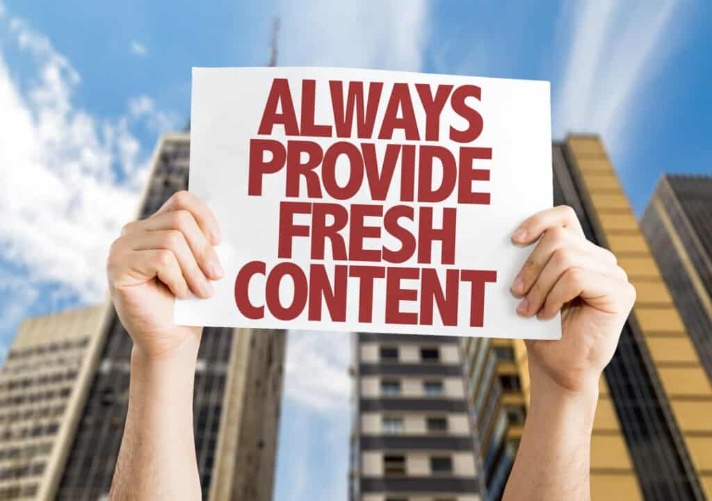 Person holding a sign that says always provide fresh content